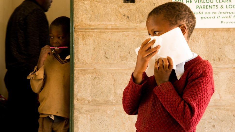 A young schoolgirl holds an ice block to her face to numb areas that will be injected with the painful treatment for cutaneou