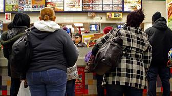 People line up to buy food at a fast food restaurant in Harlem in New York December 16, 2009. New York City officials have waged what they call a war on obesity in recent years, including banning the use of trans-fat by restaurants, but experts say improvement has been slow in low-income neighborhoods where fast food reigns and fruits and vegetables are in short supply. In Harlem, more than half of residents are overweight or obese, according to a recent report by the city Health Department. Picture taken December 16, 2009. REUTERS/Finbarr O'Reilly   (UNITED STATES - Tags: HEALTH FOOD)