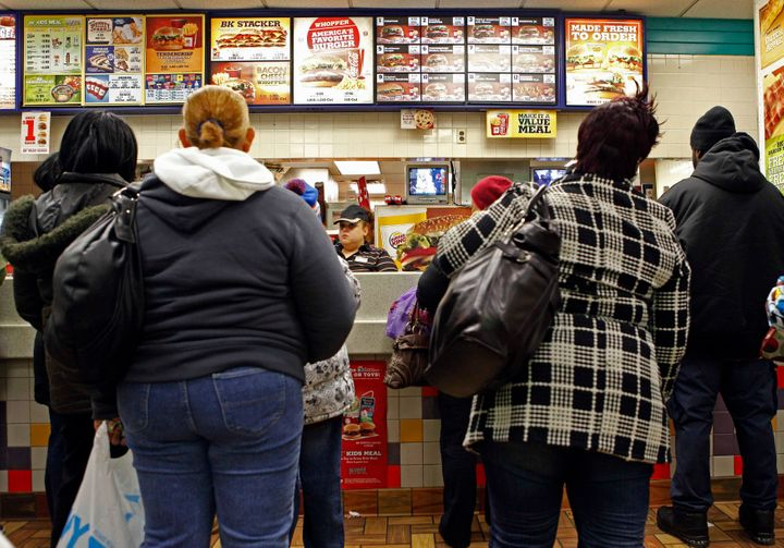 People line up to buy food at a fast food restaurant in Harlem in New York. Minority communities have been inundated with fas