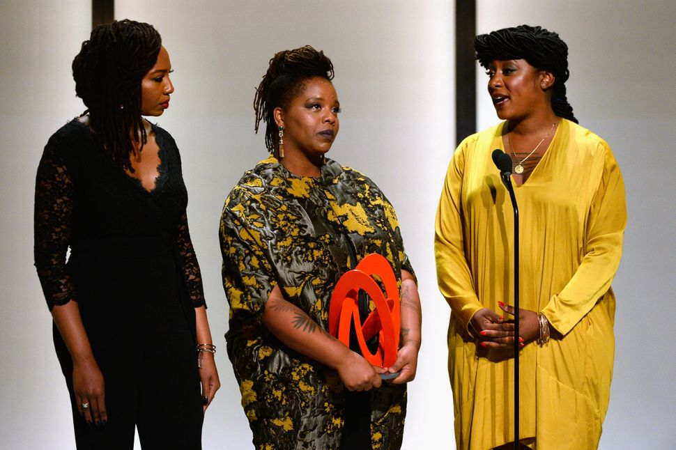 Opal Tometi, Patrisse Cullors and Alicia Garza accept an award onstage during Glamour Women of the Year 2016 for their relent