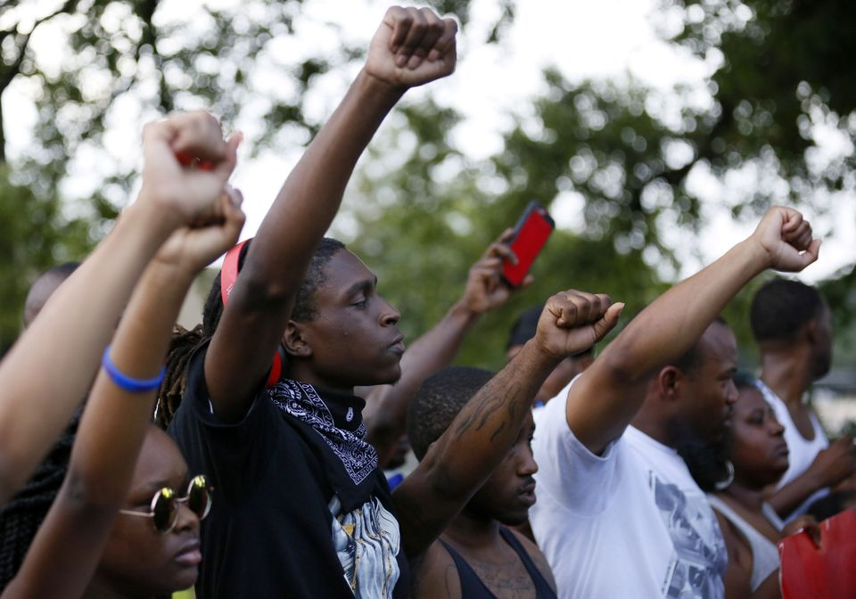 Protesters stand united with their fists raised at a Black Lives Matter