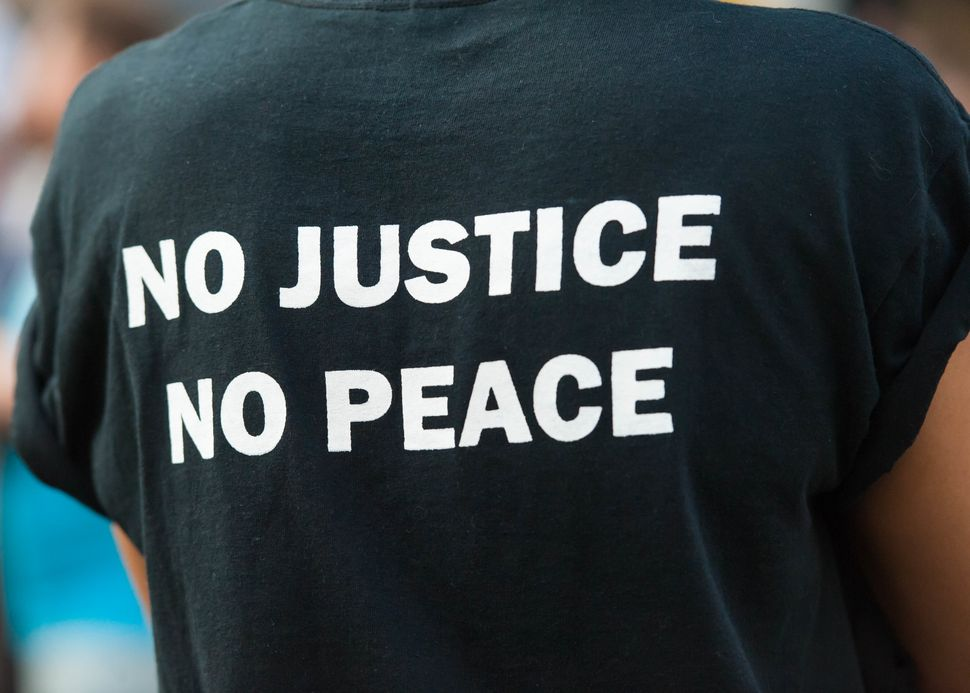 """A protester wears a T-shirt proclaiming """"No Justice, No Peace"""" as they attend a Black Lives Matter group rally."""