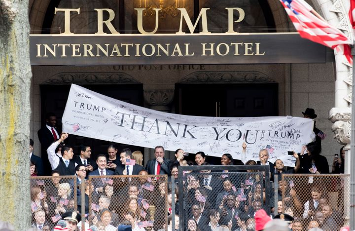 Trump International Hotel employees cheer during the Inaugural Parade on Jan. 20. His hotel has seen a boom in business from
