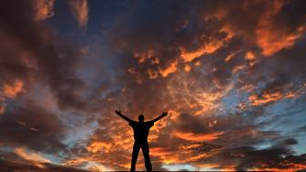 A man lifts his arms in worship against a dramatic sunset. Themes include salvation, prayer, meditation, christianity, single, reverence, praise and worship, praise, singing, outside, religious, spirituality, and hope. Man is middle aged and in rear view. Full length. Spectacular sunset sky with unaltered colours provides a dramatic and beautiful background to the image. Man is in his early 40s, caucasian, and healthy and fit. Image taken in a rural area to capture the wide, pristine sky.