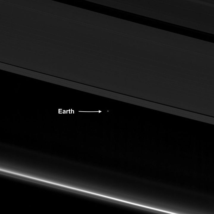 An April 12 image from NASA's Cassini spacecraft shows Earth as a point of light between the icy rings of Saturn. Cassini was