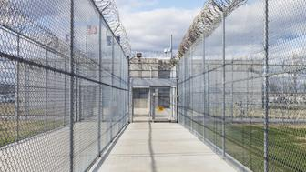 Prison fence, gate and barbed wire at a Correctional Facility