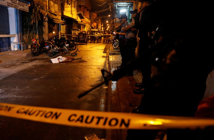 Policemen stand guard near the body of a man killed during what police said was a drug related vigilante killing in Pasig, Me