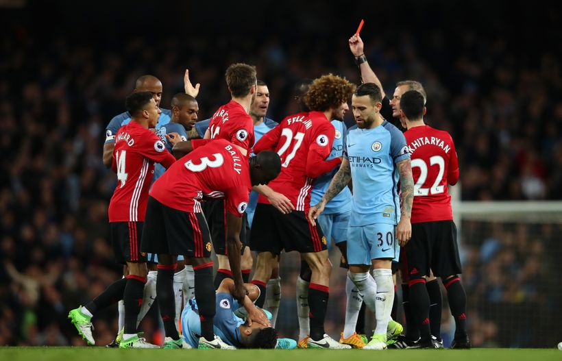 Players from both sides react as Manchester United midfielder Marouaine Fellaini is shown a red card.