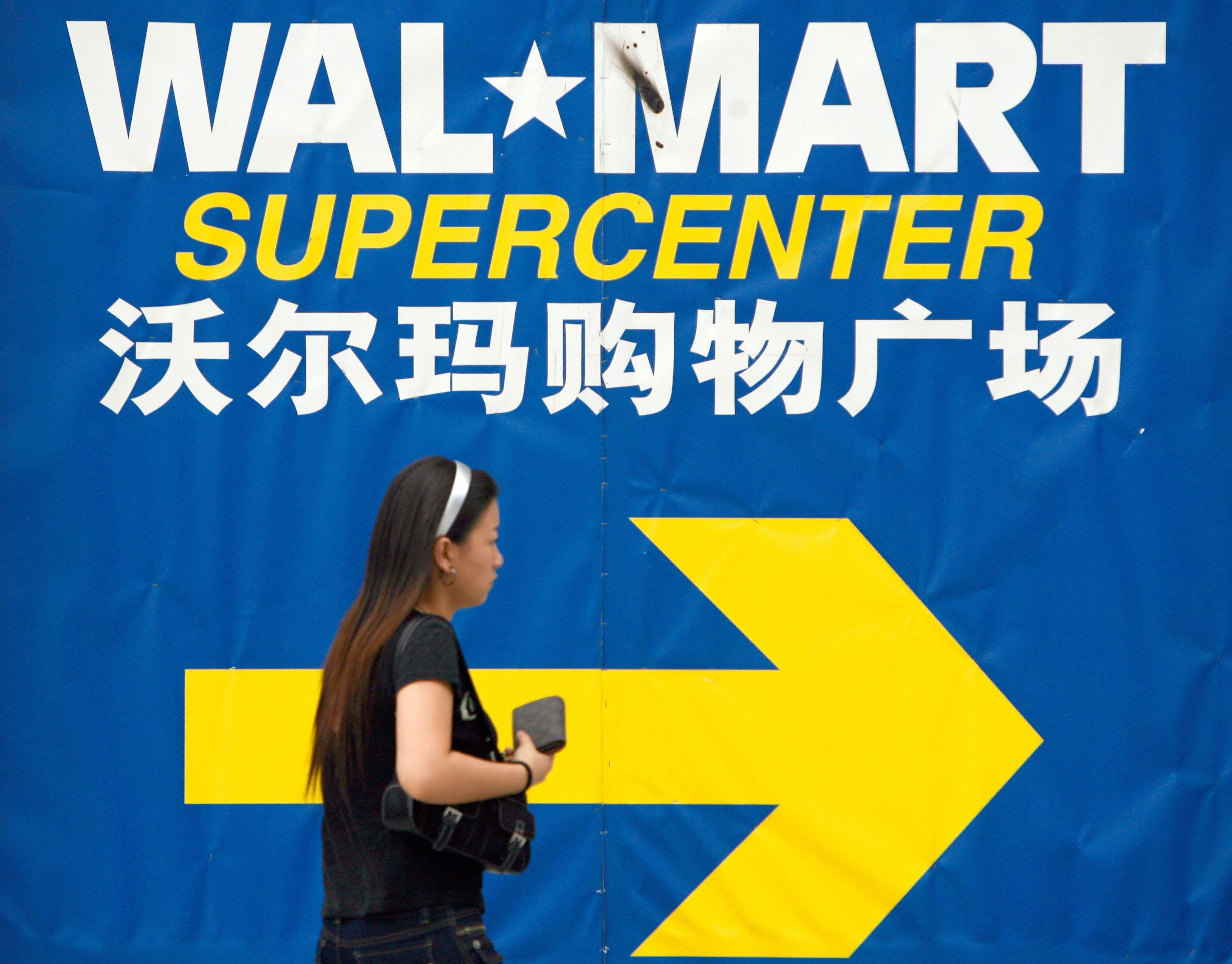 Beijing, CHINA: A pedestrian walks past a Wal-Mart signboard in Beijing, 26 July 2007. US retail giant Wal-Mart Stores Inc said on 25 July it has cautioned two of its Chinese suppliers amid allegations they exploited workers as the companies were among four accused in June of a range of labour violations in the production of official merchandise for the 2008 Beijing Olympics. AFP PHOTO/TEH ENG KOON (Photo credit should read TEH ENG KOON/AFP/Getty Images)