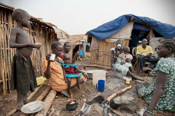 Refugees have breakfast in front of their huts in displaced persons camp, Juba, South Sudan, February 28, 2012.
