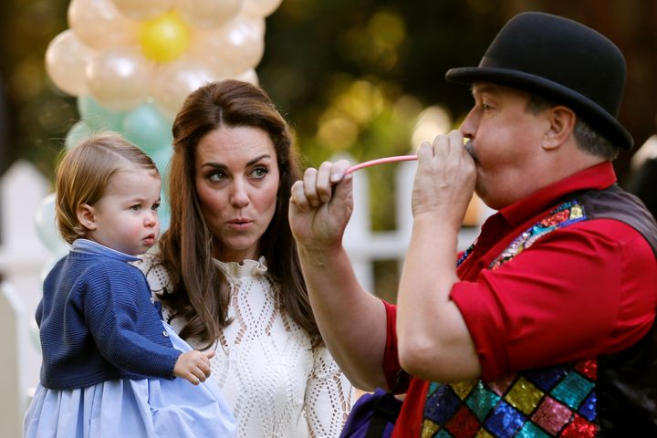 Catherine, Duchess of Cambridge, and Princess Charlotte watch a man inflate a balloon at a children's party on Sept. 29, 2016
