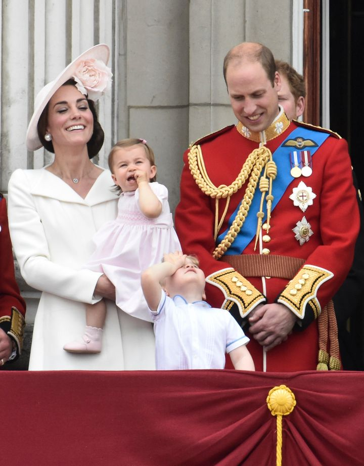 Catherine, Duchess of Cambridge holding Princess Charlotte, Prince George and Prince William, stand on the balcony of Bucking