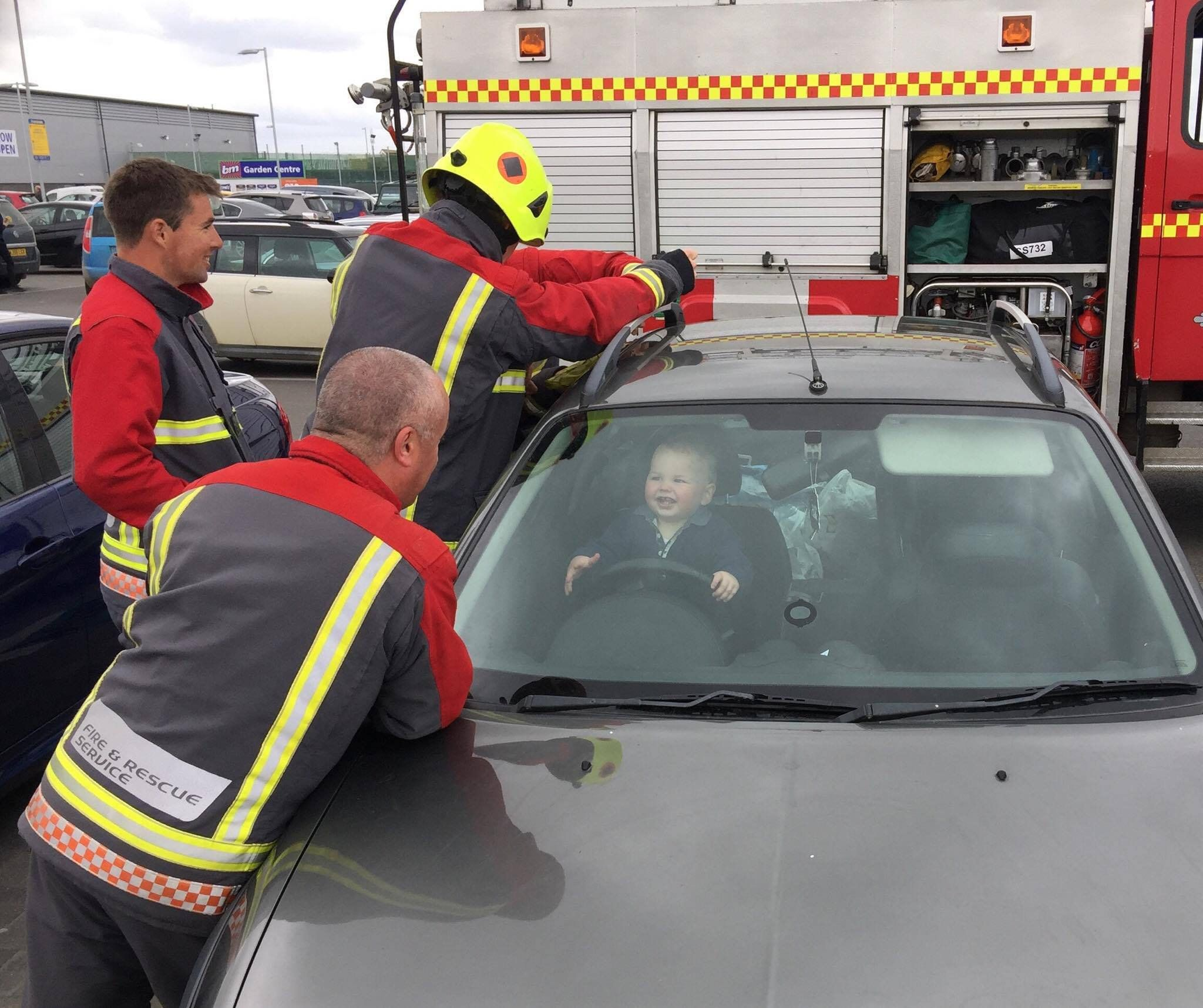 Brandon Green,18 months old locked in the car with a fire fighter keeping him entertained in Bude, Cornwall. See SWNS copy SWTOT: THIS is the heart-warming moment a toddler is entertained by a burly fireman as his colleagues battle to free him from a locked car. Little Brandon Green, 18 months, can be seen bearing a huge, adorable grin as he clutches the steering wheel of his mum's motor after accidentally locking himself in.Crews from Bude Community Fire Station responded to a call on Friday from the mother of the toddler who had accidentally got locked in the car outside Lidl in Bude, Cornwall.