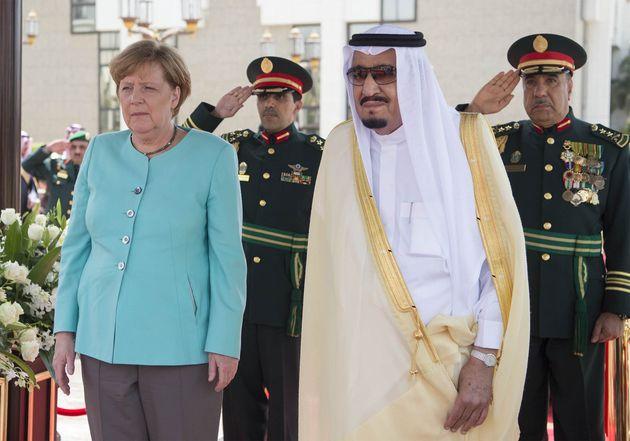 German Chancellor Angela Merkel (C) stands next to Saudi Arabia's King Salman bin Abdulaziz Al Saud (R)...