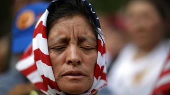 WASHINGTON, DC - MAY 01:  Viviana Perez, an immigrant from Guatemala, joins protesters in prayer at the start of a demonstration in Lafayette Park while denouncing U.S. President Donald Trump's anti-immigrant policies May 1, 2017 in Washington, DC.  Protests around the nation were held to coincide with May Day.  (Photo by Win McNamee/Getty Images)