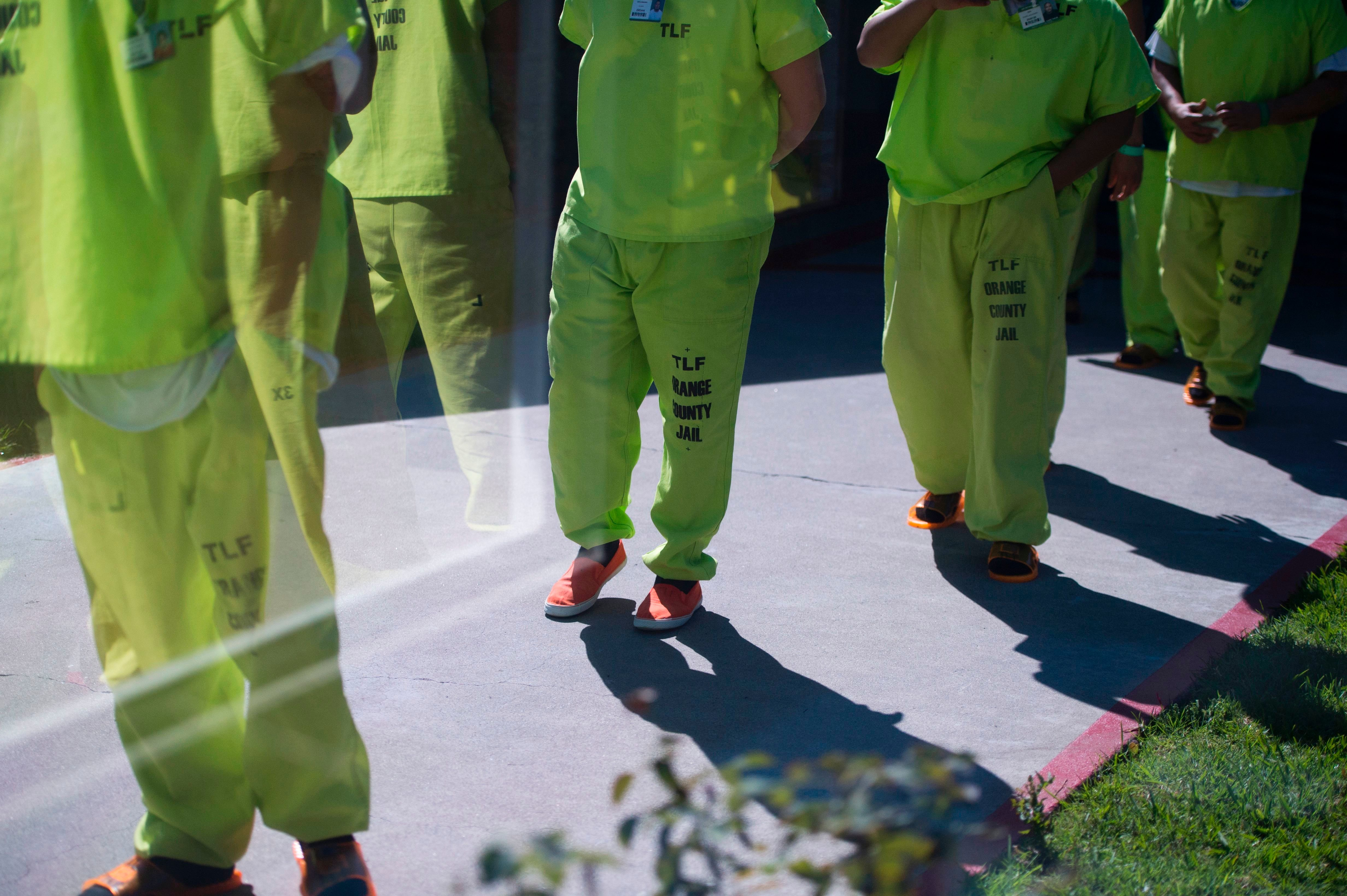 Men wearing neon-colored jail clothes signifying immigration detainees walk to pick up their lunches at the Theo Lacy Facility, a county jail which houses convicted criminals as well as immigration detainees, March 14, 2017 in Orange, California, about 32 miles (52km) southeast of Los Angeles. US President Donald Trumps first budget provides more than USD 4.5 billion in new spending to fight illegal immigration by adding immigration and border enforcement agents, prosecutors and judges, as well as building a wall on the border with Mexico. / AFP PHOTO / Robyn Beck        (Photo credit should read ROBYN BECK/AFP/Getty Images)