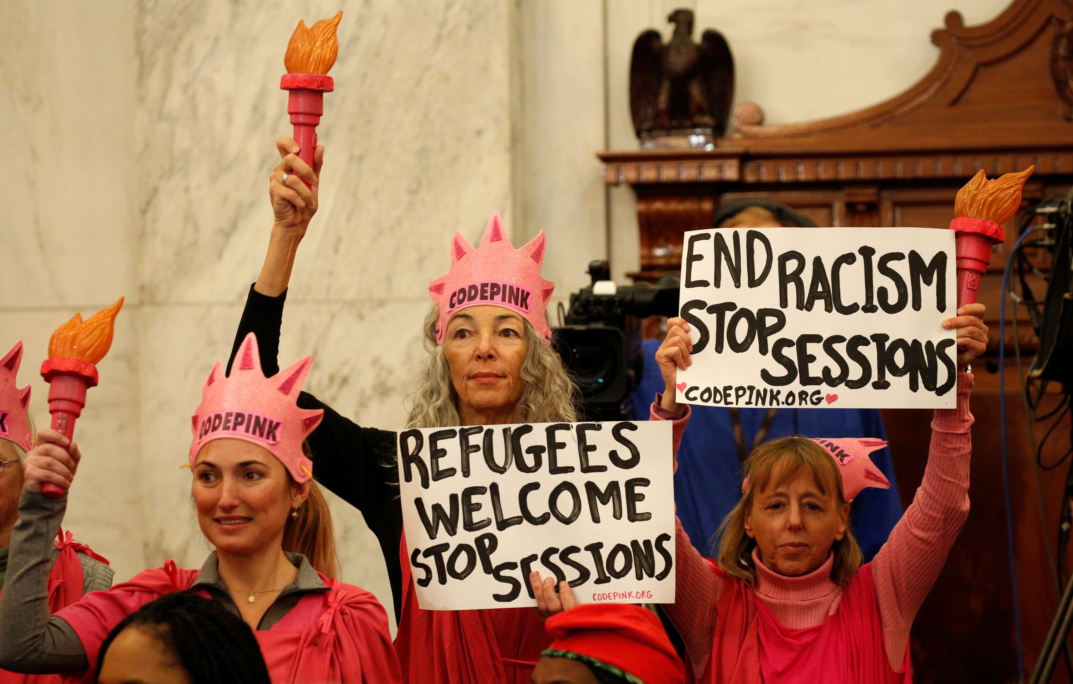 Protesters hold signs at the Senate Judiciary Committee confirmation hearing for U.S. Sen. Jeff Sessions (R-AL) to become U.S. attorney general on Capitol Hill in Washington, U.S. January 10, 2017. REUTERS/Kevin Lamarque