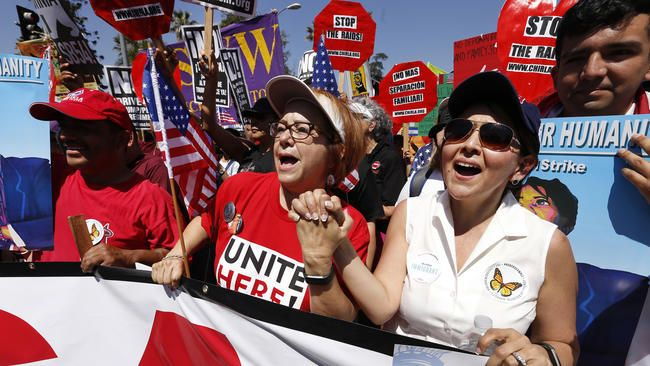 Maria Elena Durazo, center, labor leader, hold hands with immigration attorney Jessica Dominguez, right, in a May Day march