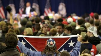 A supporter of Republican presidential candidate Donald Trump holds up a Confederate flag prior to his campaign rally in Manassas, Virginia December 2, 2015. The man was removed from the rally by local authorities.        REUTERS/Gary Cameron