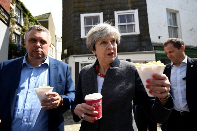 Theresa May enjoys some chips during a campaign stop on May 2, 2017 in Mevagissey,