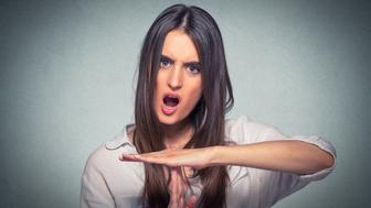 Young woman showing time out hand gesture, frustrated screaming to stop isolated on gray background. Human emotions face expression reaction