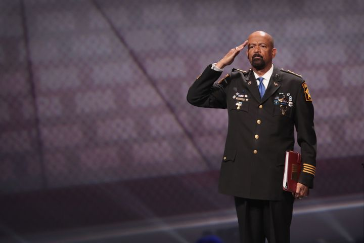 David Clarke Jr., sheriff of Milwaukee County in Wisconsin, salutes as he leaves the stage after speaking at the NRA-ILA