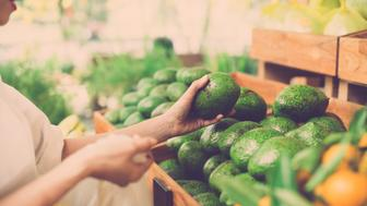 Cropped image of a customer choosing avocados in the supermarket
