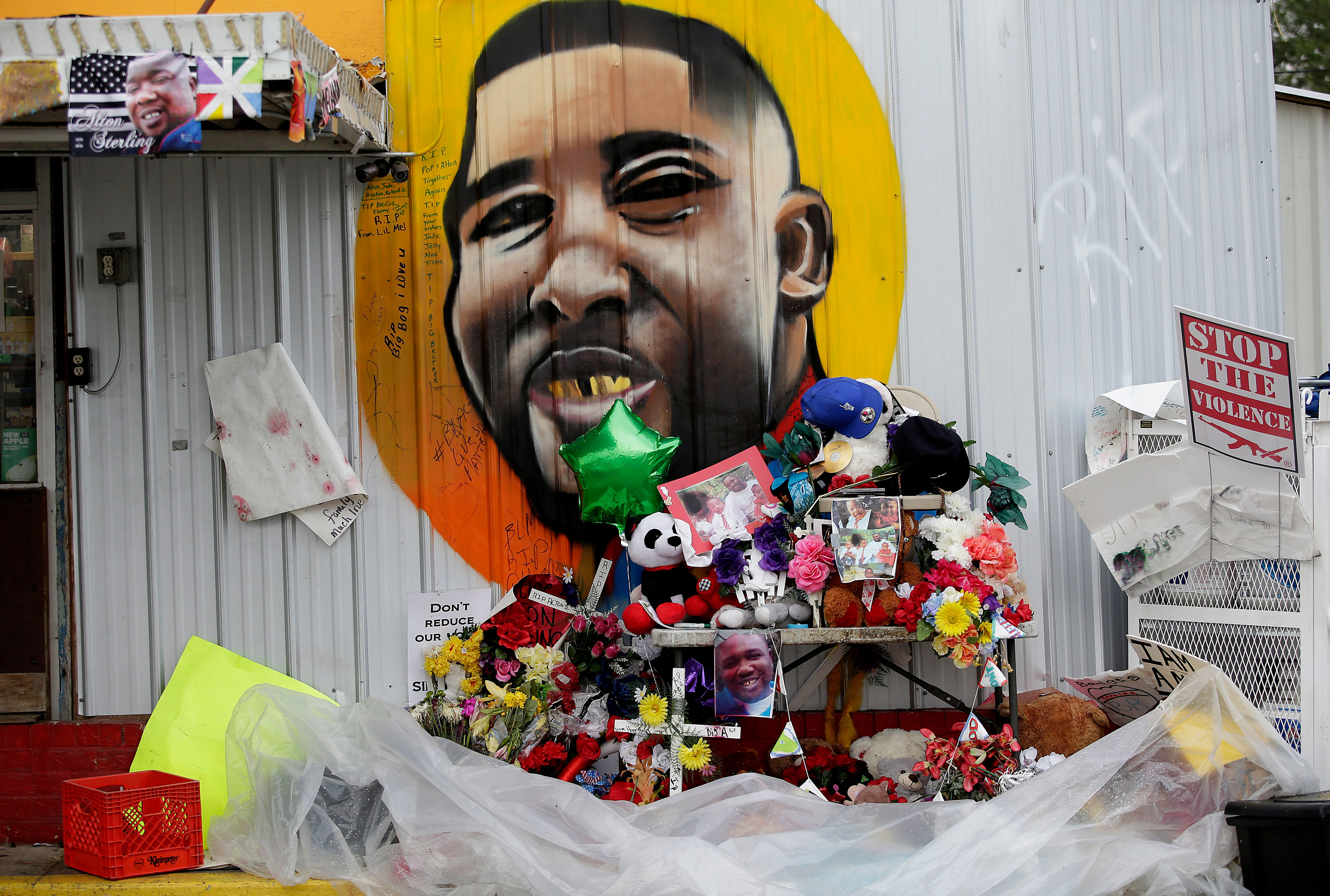 A makeshift memorial for the fatal police shooting of Alton Sterling outside the Triple S Food Mart next to a mural of Sterli