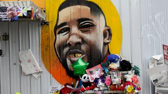 BATON ROUGE, LA - JULY 21: A makeshift memorial for the fatal police shooting of Alton Sterling is displayed outside the Triple S Food Mart next to a mural of Sterling July 21, 2016 in Baton Rouge, Louisiana. Sterling was fatally wounded outside the Triple S Food Mart on July 5 by a Baton Rouge police officer who was responding to a dispatch call of a man with a gun. Local communities are also reeling in the aftermath of the recent killings of three police officers who were ambushed along Baton Rouge's Airline Highway Sunday. (Photo by Joshua Lott/Getty Images)