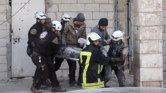 Syrian civil defence volunteers, known as the White Helmets, carry a comrade who was injured in an air strike while searching for victims of a previous raid in the rebel-held town of Binnish, on the outskirts of Idlib, on February 25, 2017. / AFP / Omar haj kadour        (Photo credit should read OMAR HAJ KADOUR/AFP/Getty Images)