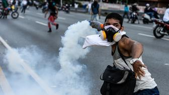 An opposition activist clashes with the riot police during a march against Venezuelan President Nicolas Maduro held on May Day, in Caracas on May 1, 2017.  Venezuela's beleaguered President Nicolas Maduro on Monday called for a new constitution, to be written by a 'people's' body circumventing the opposition-held Congress. The decree was to 'block the fascist coup' threatening the country, he told thousands of supporters in Caracas at a May Day rally.   / AFP PHOTO / Federico PARRA        (Photo credit should read FEDERICO PARRA/AFP/Getty Images)
