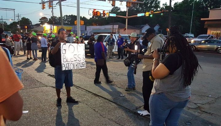 People stand gathered and holding signs on Tuesday outside of the store where Sterling was shot.