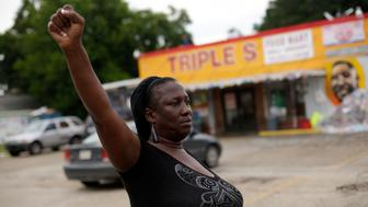 BATON ROUGE, LA - JULY 21: Veda Washington protest the fatal police shooting of her nephew Alton Sterling outside the Triple S Food Mart July 21, 2016 in Baton Rouge, Louisiana. Sterling was fatally wounded outside the Triple S Food Mart on July 5 by a Baton Rouge police officer who was responding to a dispatch call of a man with a gun. Local communities are also reeling in the aftermath of the recent killings of three police officers who were ambushed along Baton Rouge's Airline Highway Sunday. (Photo by Joshua Lott/Getty Images)