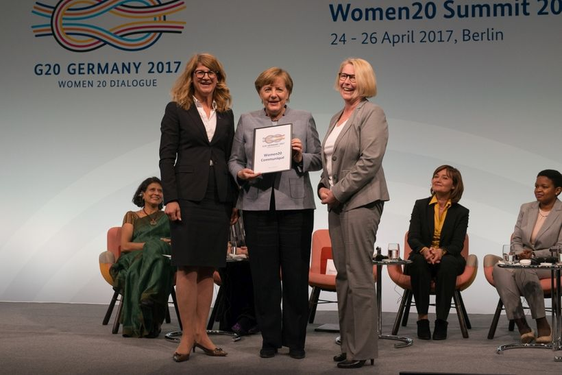 German Chancellor Angela Merkel is handed the Women 20 communiqué in Berlin on 26 April.