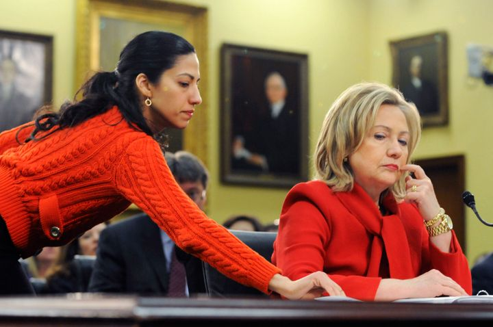 U.S. Secretary of State Hillary Clinton (R) receives a note from her aide Huma Abedin (L) as she testifies during a hearing o