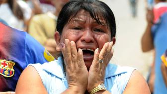 A woman cries at the crime scene in which five people -- including a high school student -- were shot dead in the suburb of La Haya, in northern Tegucigalpa, on April 15, 2013. In March 2012, the UN announced Honduras had the world's highest murder rate, at 82.1 deaths per 100,000 people, while a local observatory on violence put the rate at 86.5 per 100,000.  AFP PHOTO/Orlando SIERRA        (Photo credit should read ORLANDO SIERRA/AFP/Getty Images)