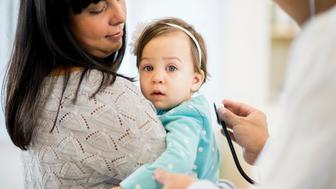 A little girl being held by her mother at the doctors office as the doctor checks her heartbeat.