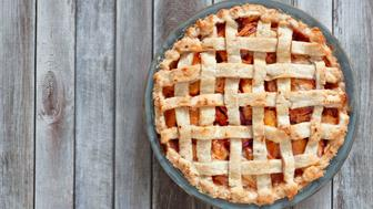 Rustic homemade peach pie in baking plate, above view on a wood background