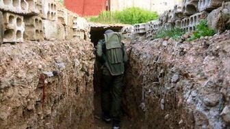 An opposition forces member breaks through in a tunnel as clashes between opposition forces and Assad regime forces continue in Jobar and Qaboun district of Damascus Syria on March 22 2017