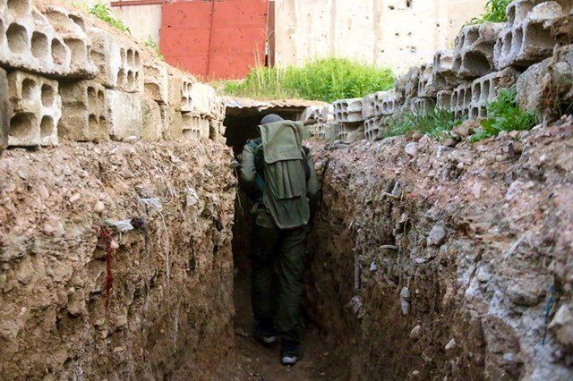 An opposition forces member breaks through in a tunnel as clashes between opposition forces and Assad regime forces continue