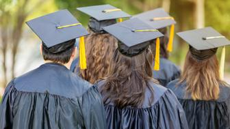 Diverse college graduates listen to speaker during graduation. They are wearing black caps and gowns with yellow tassels. Their backs are to the camera.