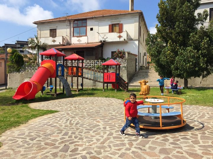 Ayan and Atya's children, Ahmad, 3 (foreground) and Ali, 8 (running) playing in a park in Riace, Italy.