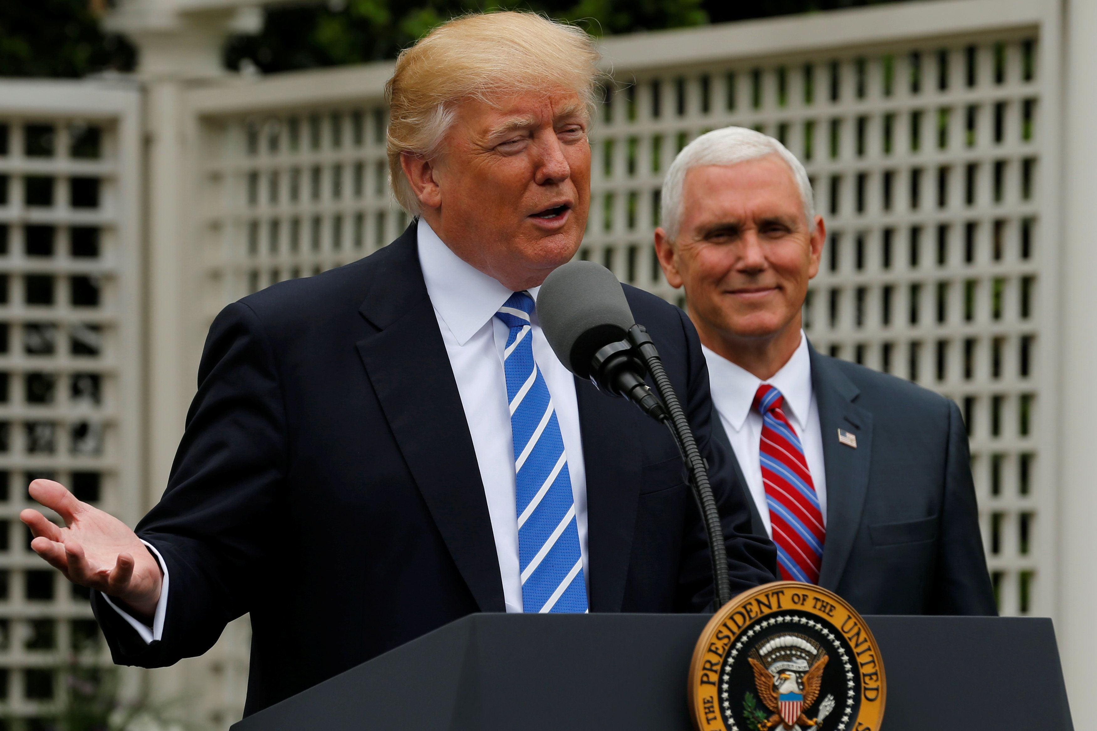 U.S. President Donald Trump (L), flanked by Vice President Mike Pence (R), delivers remarks to members of the Independent Community Bankers Association in the Kennedy Garden at the White House in Washington, U.S., May 1, 2017.  REUTERS/Jonathan Ernst