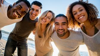 Happy group of friends at the beach hugging in a circle and looking at the camera smiling
