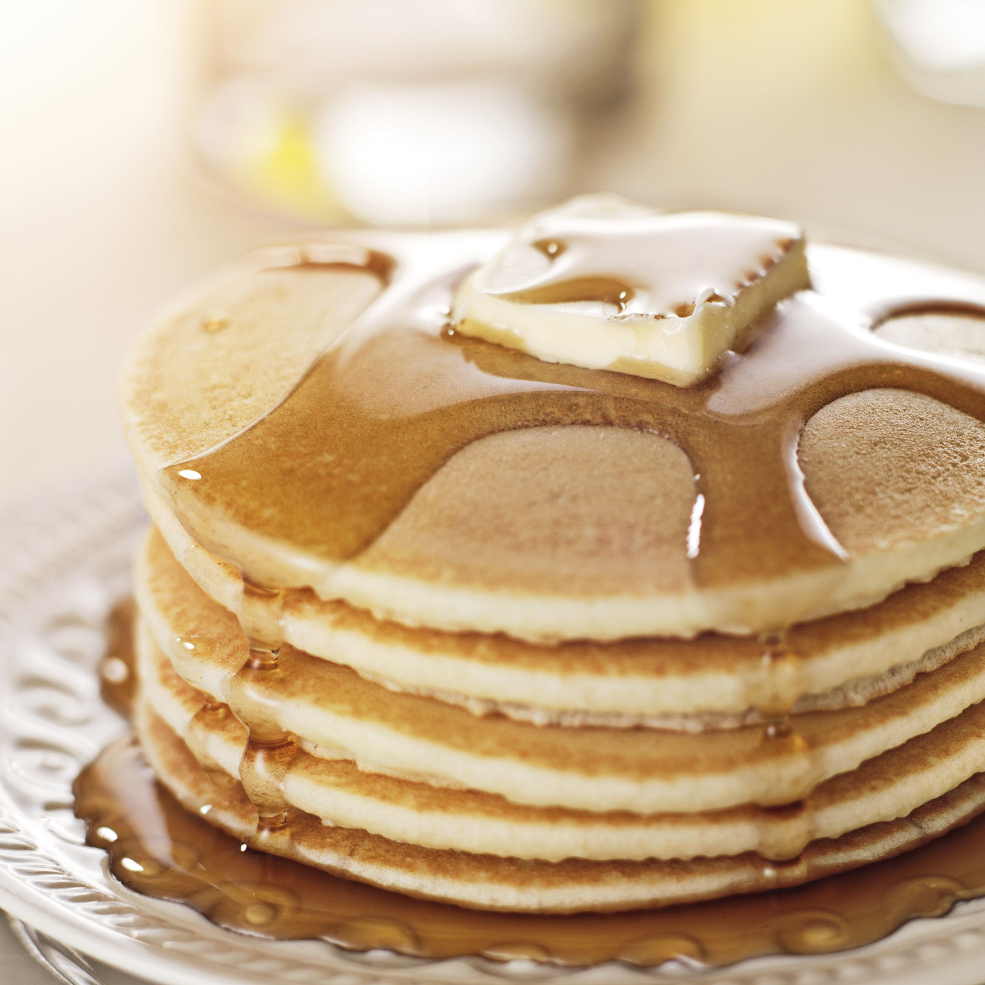 close up photo of a  stack of pancakes with syrup and butter. Shot with selective focus