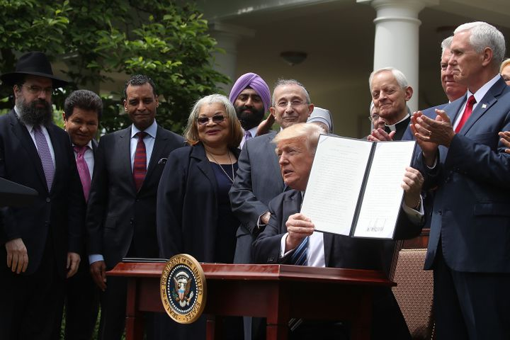 President Donald Trump is flanked by clergy members after signing an Executive Order on Promoting Free Speech and Religious L