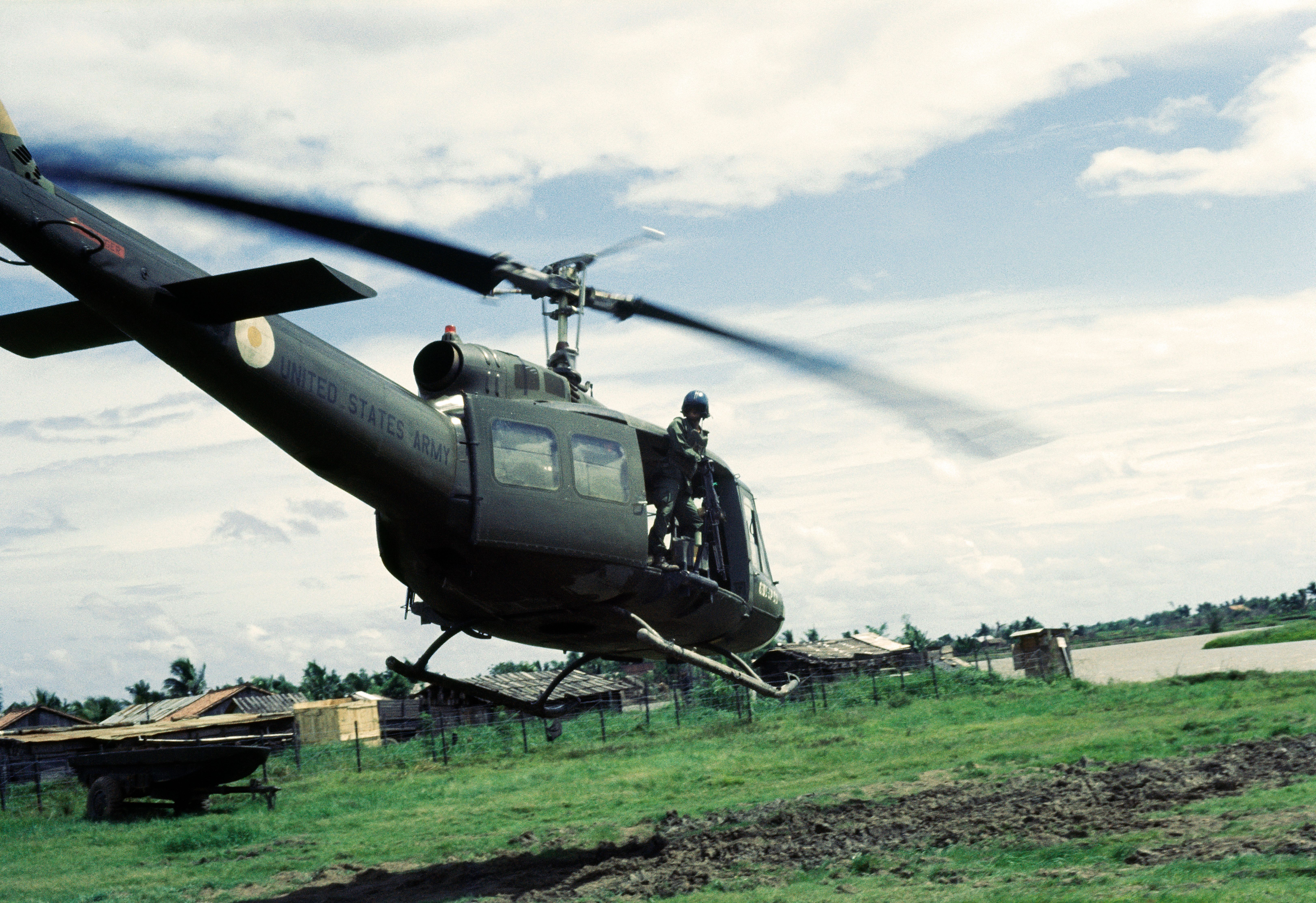 July 1967 - A door gunner surveys the area from the open door of his Huey helicopter as they fly close to the ground in the Mekong Delta during the Vietnam war. (Photo by ANDREW HOLBROOKE/Corbis via Getty Images)