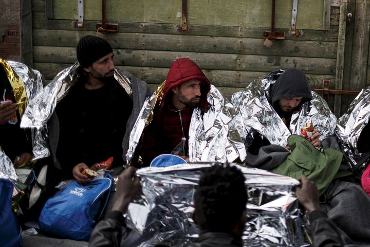Refugees and migrants are covered with thermal blankets and receive food following a rescue operation at open sea near the is