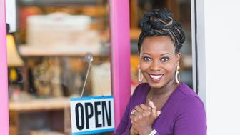 A young African American woman standing at the front door of her small business. An OPEN sign hangs on the glass door. Her small braids of her long hair are tied up in a bun in a unique hairstyle. She is looking at the camera, smiling and confident.