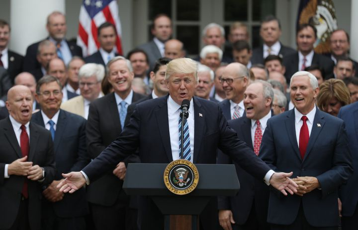 President Donald Trump gathers with Vice President Mike Pence, right, and gleeful congressional Republicans in the White Hous
